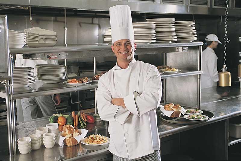 Chef posing in kitchen of restaurant